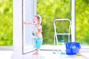 Cute laughing curly toddler girl washing a big window